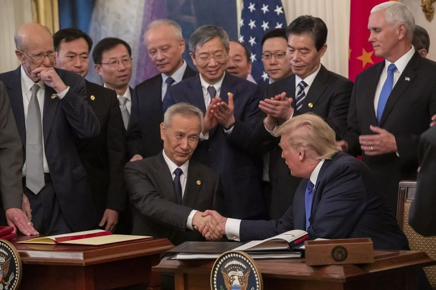 Chinese Vice Premier Liu He (left) and US President Donald Trump (right) participate in the trade deal signing ceremony.