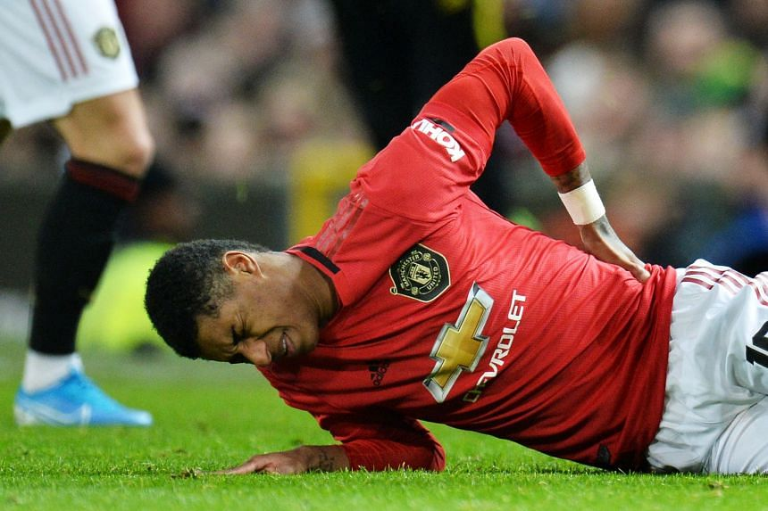 Marcus Rashford holds his back in pain during the match against Wolves.