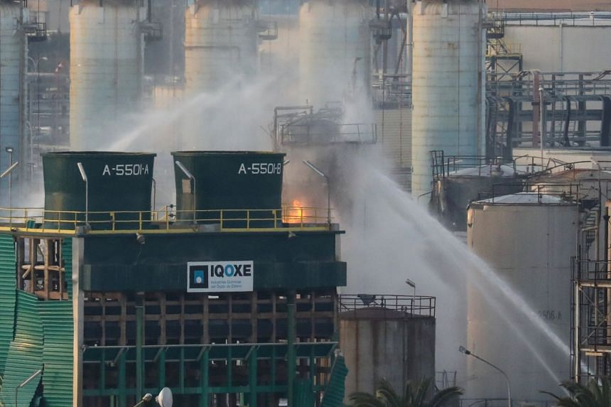 Firefighters spray water after a the blast at the chemical factory in Tarragona, Spain.
