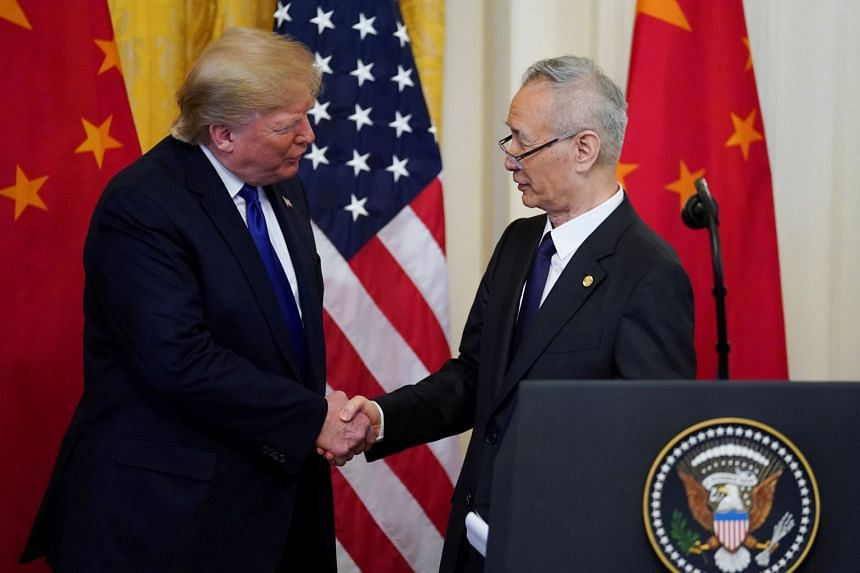 """US President Donald Trump (left) shakes hands with Chinese Vice-Premier Liu He during a signing ceremony for """"Phase One"""" of the US-China trade agreement."""