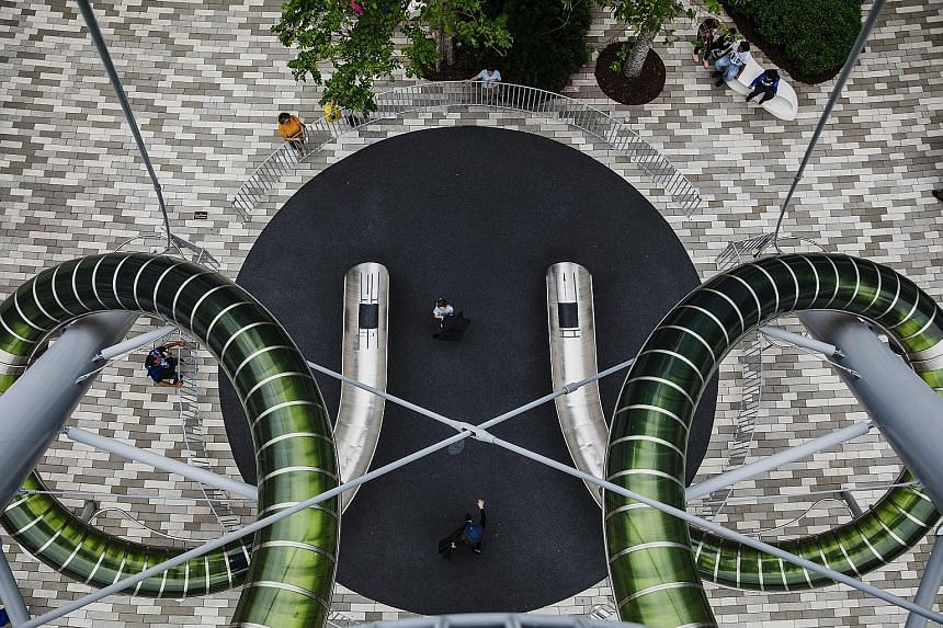 The Aventura Mall in Florida invites children and adults to take rides on its nine-storey slide (left) and has installed whimsical sculptures such as the Walking Figure (below). It emphasises low-tech entertainment over cutting-edge gadgetry to beat
