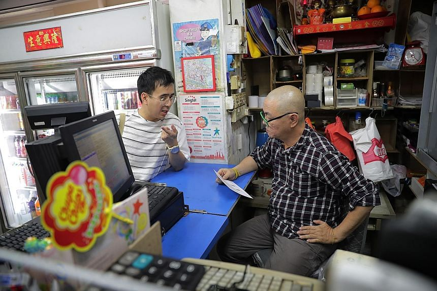 Film-maker Jun Chong (left) chatting with Mr Lee Kin Pang, 57, an employee at Chai Yu Trading in Sin Ming Avenue, to raise awareness about his short film, New Resident. He will be handing postcards carrying details of the film to about 1,200 househol