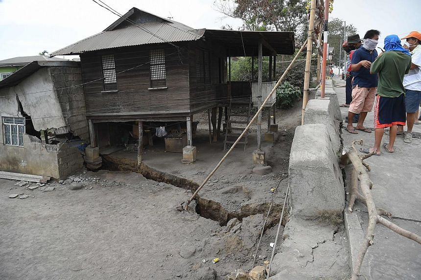 A resident pointing to a fissure by his house in Lemery town, Batangas province, caused by tremors from Taal volcano's activity.