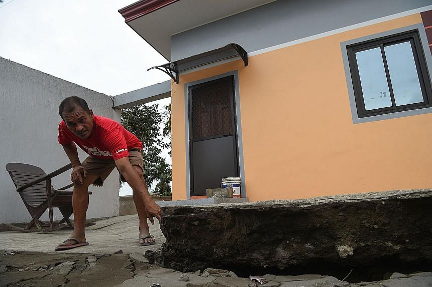 A house standing on a fissure caused by Taal volcano's activity in Lemery town yesterday. The Philippine authorities are struggling to keep thousands of evacuees from returning to their homes in areas threatened by a massive eruption of the volcano.