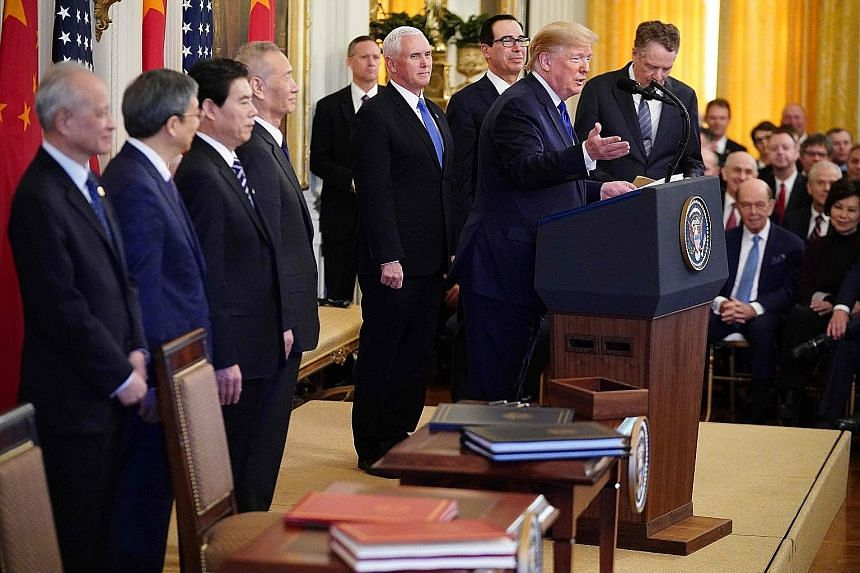 US President Donald Trump addressing a press conference at the White House before signing the deal with China. Beside him are China's Vice-Premier Liu He (fourth from left) and US Vice-President Mike Pence.