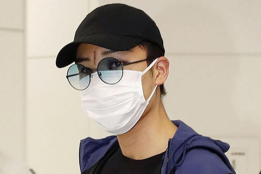 Japanese top-ranked shuttler Kento Momota, wearing a mask, arriving at Narita Airport after his flight from Malaysia.