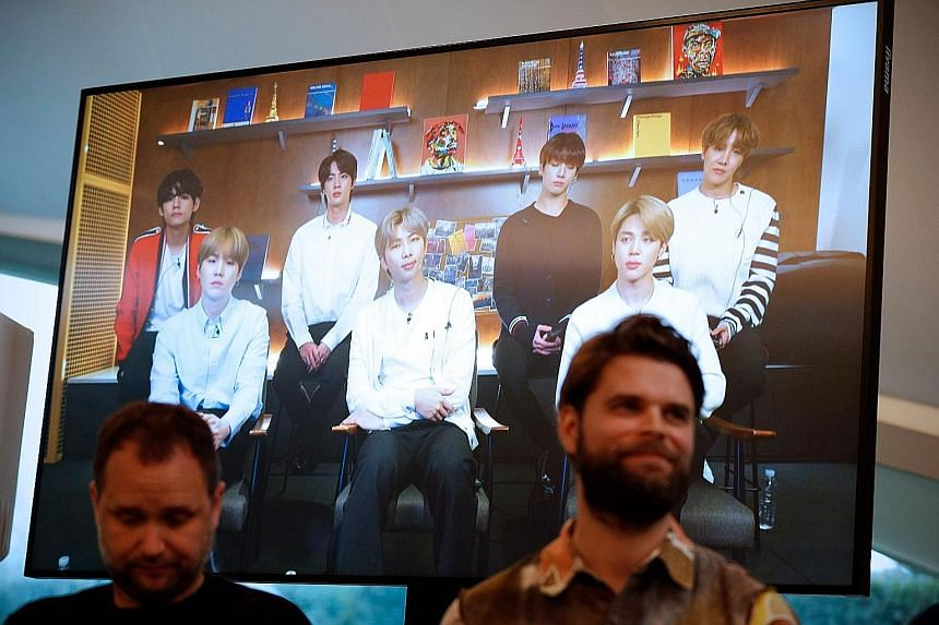 Danish artist Jakob Kudsk Steensen (right) sits in front of a monitor live-streaming South Korean boy band BTS during the announcement of his new work, Catharsis, at the launch of the global public art project Connect, BTS in London on Tuesday.