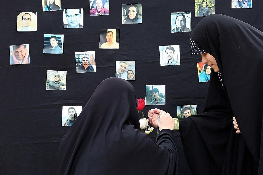 Part of the wreckage of the Ukrainian plane that was shot down outside Teheran on Jan 8, killing all 176 people on board. PHOTO: AGENCE FRANCE-PRESSE Iranian students lighting a candle during a memorial ceremony in Teheran on Tuesday for the passenge