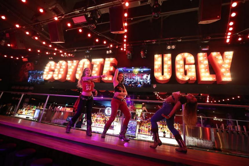 Dancers from bar-restaurant Coyote Ugly Saloon, dancing on the bar top at the newest outlet at Clarke Quay as our podcasters highlight it as a place to visit in this Life Picks podcast.