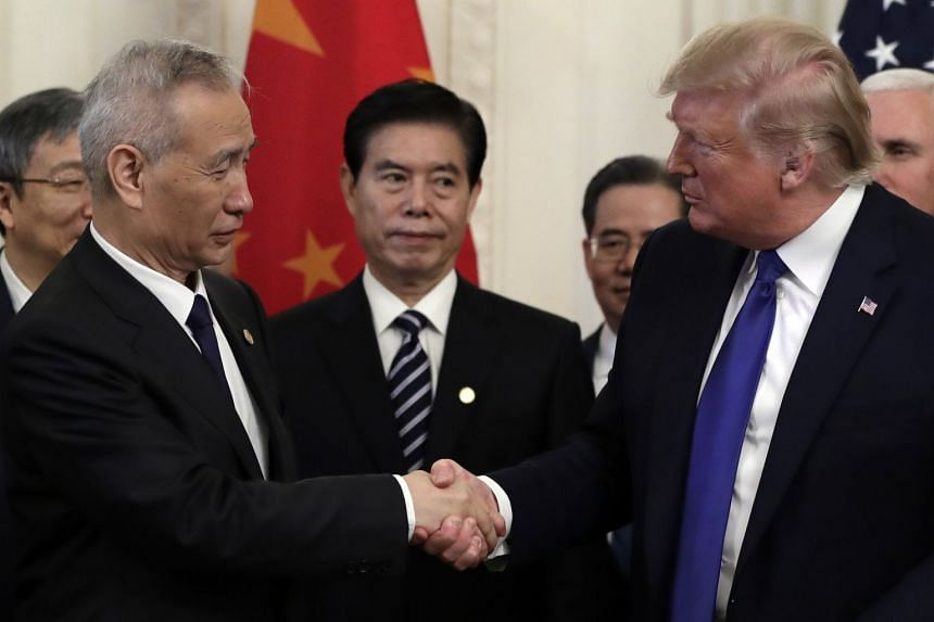 President Donald Trump shakes hands with Chinese Vice-Premier Liu He after signing the agreement.