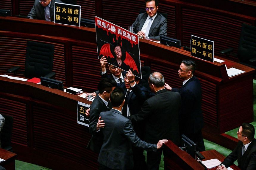 Pro-democracy lawmaker Kwok Ka Ki holds a sign as he is removed from the legislature in Hong Kong on Jan 16, 2020.