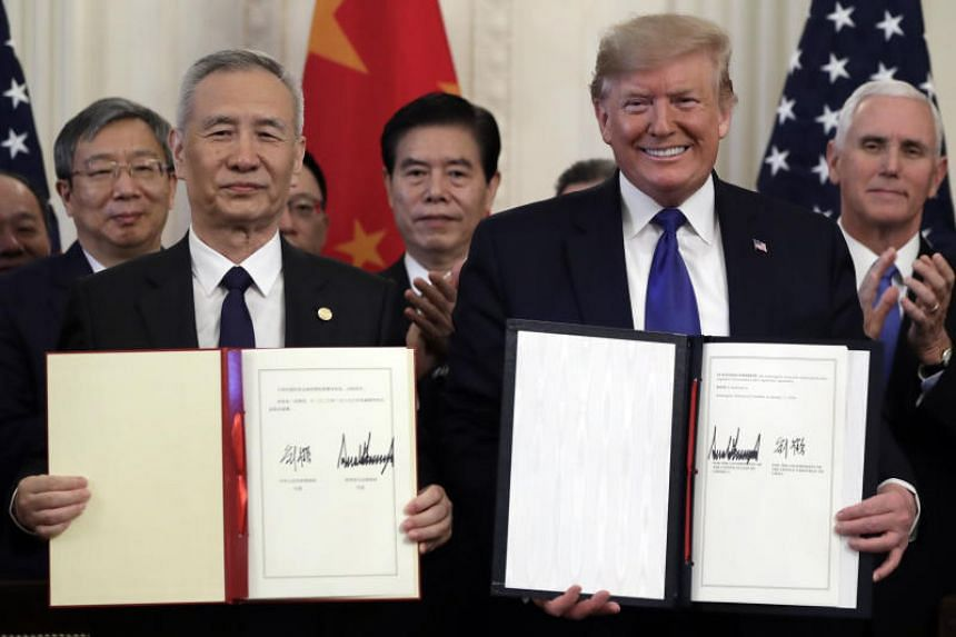 Chinese Vice-Premier Liu He signs a trade agreement with US President Donald Trump in the White House on Jan 15, 2020.