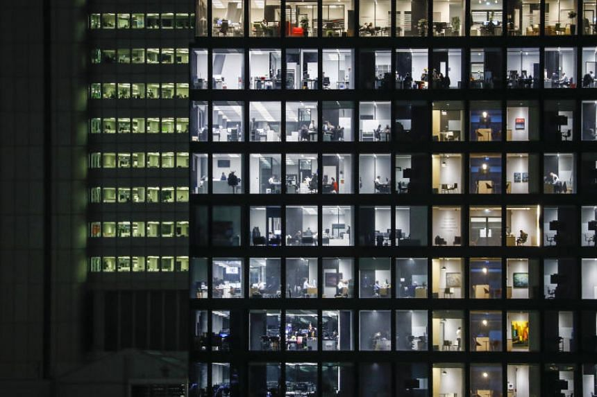 In a photo taken on Jan 13, 2020, people work in illuminated offices in Frankfurt's financial district.