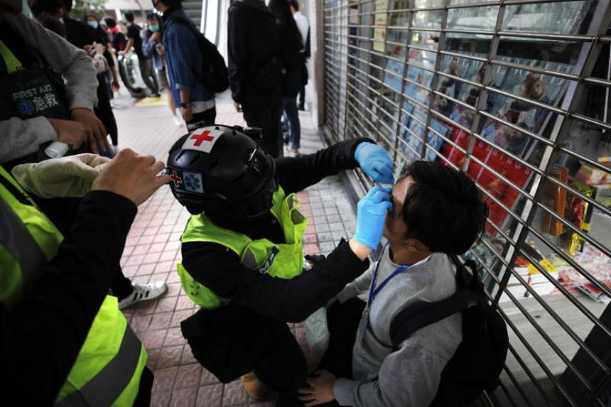 Volunteer first aid medics treat a man as protesters march in Sheung Shui near the Chinese border in Hong Kong, on Jan 5, 2020.