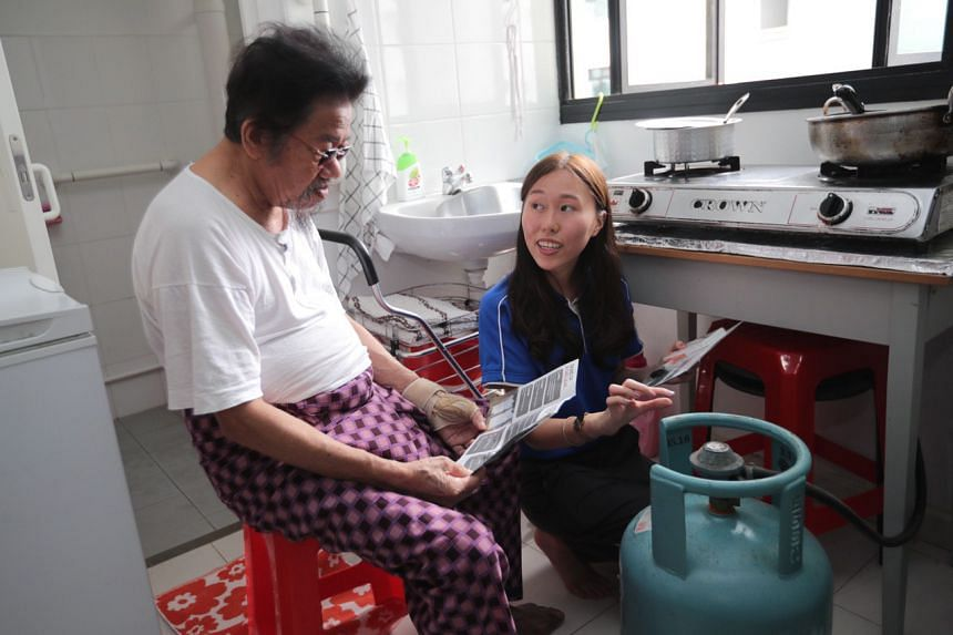 Gas operations engineer Lydia Koh (right) instructs resident Samat Bin Sakek on how to use gas appliances safely in the household.