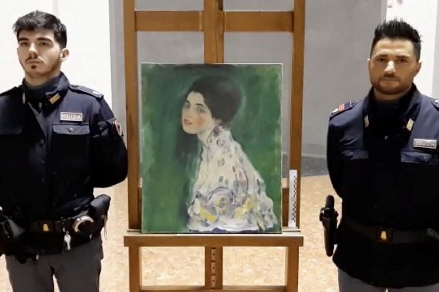 """Italian police stand next to what they say is a masterpiece by Austrian artist Gustav Klimt, """"Portrait of a Lady""""."""