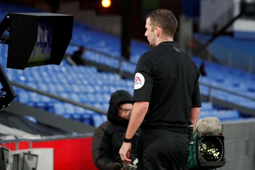 Referee Michael Oliver checks the VAR pitchside monitor before showing a red card to Crystal Palace's Luka Milivojevic.