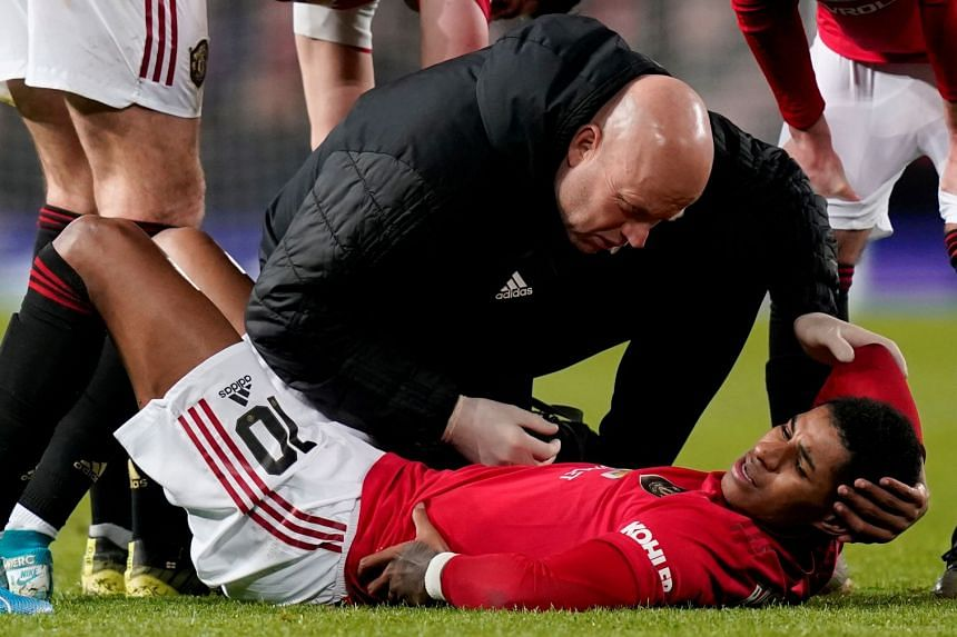 Rashford receives medical attention after sustaining an injury against Wolves.