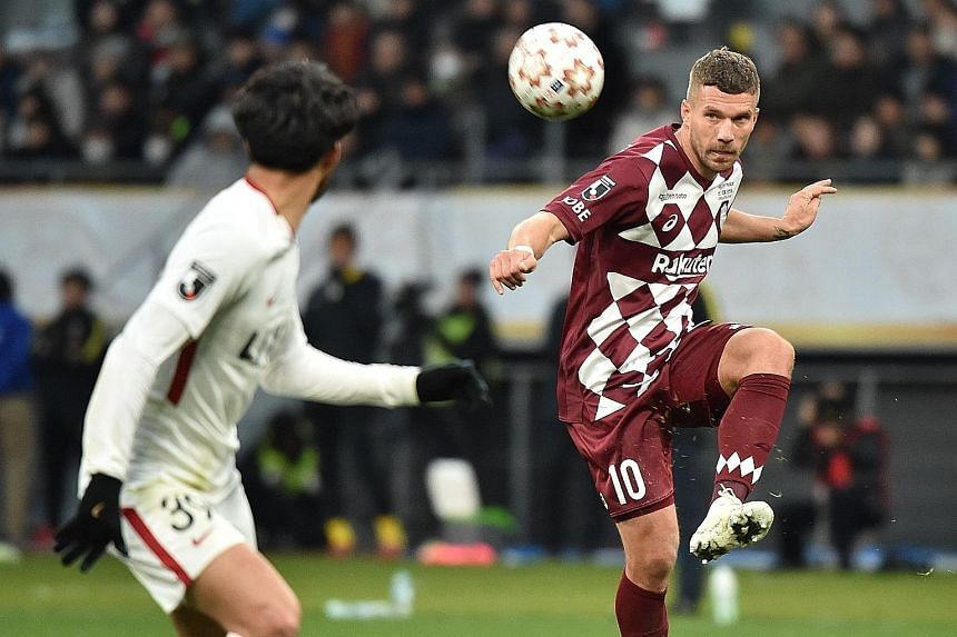 Top: Vissel Kobe forward Lukas Podolski attempting to get the better of Kashima Antlers defender Tomoya Inukai in the Emperor's Cup final in Tokyo earlier this month. Vissel Kobe won 2-0 even though a Podolski goal was ruled out. Above: Podolski posi