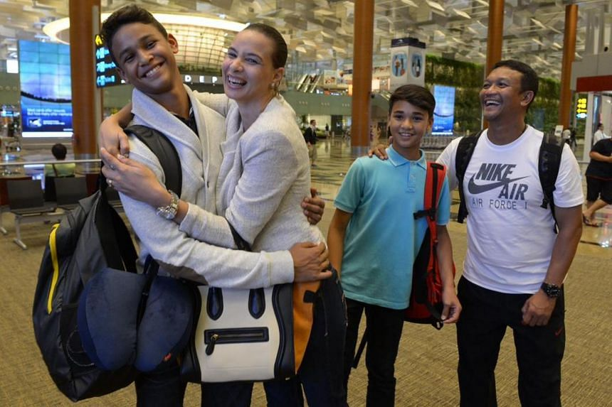 In a photo taken on March 10, 2013,  Irfan Fandi gets a farewell hug from his mother, Wendy Jacobs, at Changi Airport. Looking on are younger brother Ikhsan and father Fandi Ahmad (right).