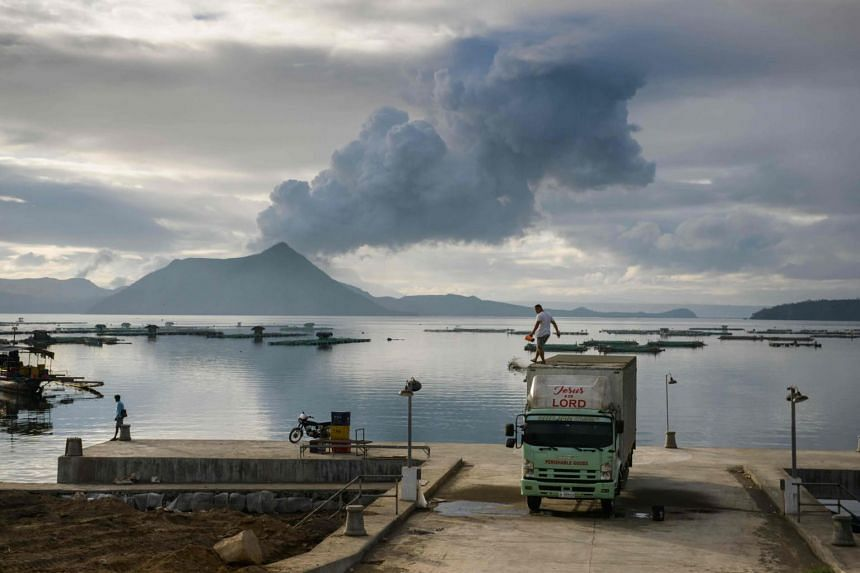 A man clears ash from the roof of his truck, as a plume of steam rises from the Taal volcano, at a fishing harbour in Laurel on Jan 17, 2020.