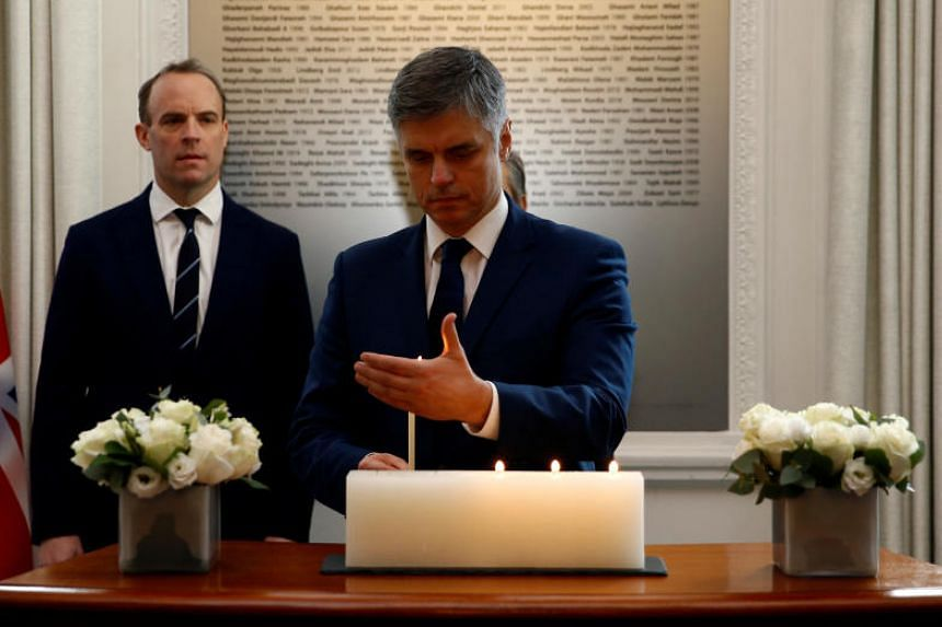 Ukrainian Foreign Minister Vadym Prystaiko lights a candle during a moment of silence ahead of a meeting for the families of the victims of the Ukraine International flight which crashed in Iran, at the High Commission of Canada in London, on Jan 16,