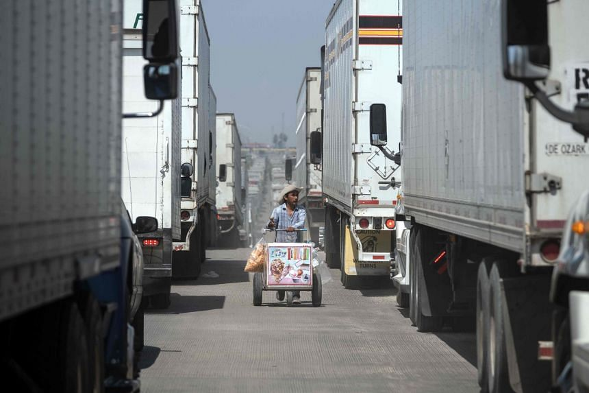 A street vendor sells ice-cream to cargo truck drivers lining up to cross to the US from Mexico.