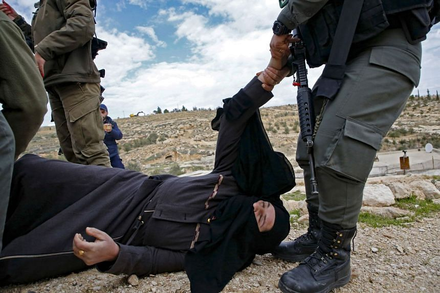 A member of the Israeli security forces pulls the arm of a woman lying on the ground during scuffles following the demolition of a Palestinian home which Israeli authorities said was built without a permit in the village of Al-Dirat near the West Ban