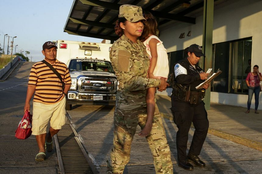 Mr Jose Gonzalez (left) follows his five-year-old daughter, carried by a police officer, in Panama on Jan 16, 2020. Mr Gonzalez's wife and five of their children are among seven people killed in a religious ritual.