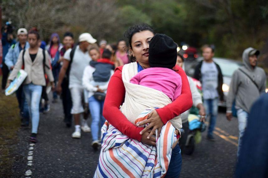 Honduran migrants walk in a caravan heading to the US, near Quezaltepeque, Guatemala, on Jan 17, 2020.