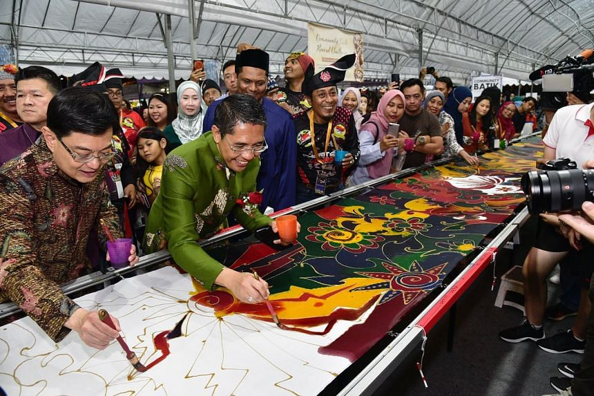 Deputy Prime Minister Heng Swee Keat and Dr Maliki Osman, Mayor of South East District and adviser to Wisma Geylang Serai, during a community batik painting event at the first anniversary celebration of the Wisma Geylang Serai.