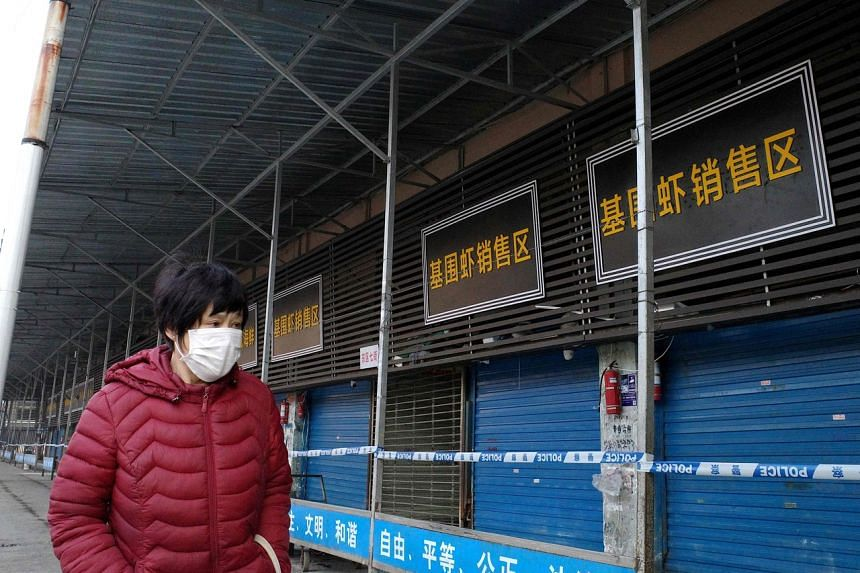 A woman walks in front of the Huanan Seafood Wholesale Market, where health authorities said a man who died from a respiratory illness had purchased goods from, in the city of Wuhan, on Jan 12, 2020.