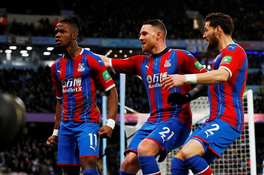 Palace's Wilfried Zaha celebrates with team mates after City's Fernandinho scored an own goal and Crystal Palace's second.