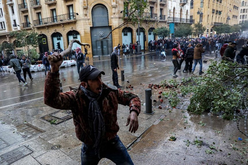 An anti-government protester swings a tree branch as others are sprayed by security forces' water cannon during clashes in Beirut.