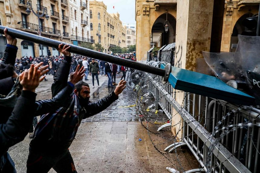 Anti-government protesters use a road sign to ram security forces taking cover during clashes in Beirut.