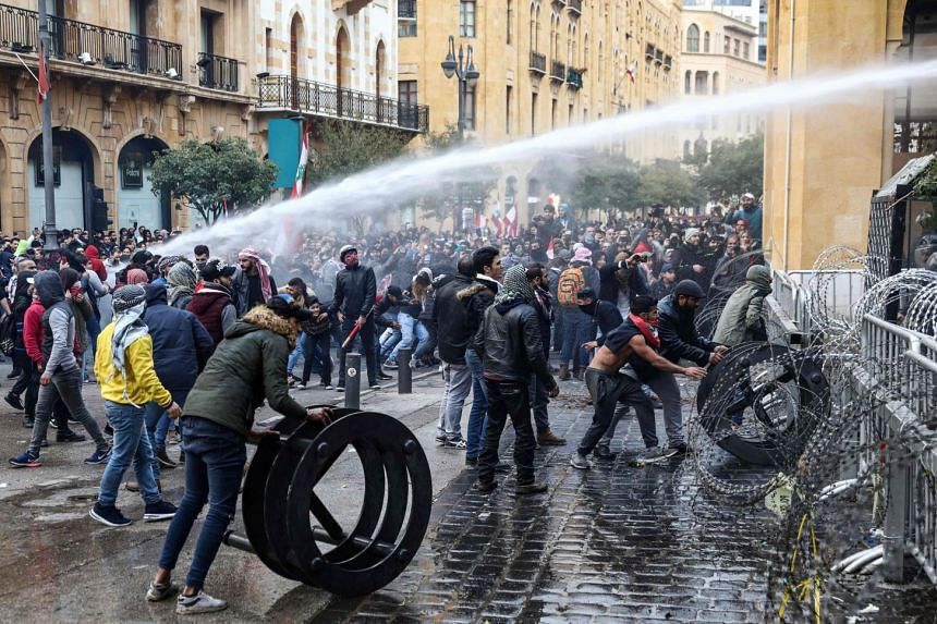 Lebanese security forces spray water cannon at anti-government protesters during clashes in Beirut.