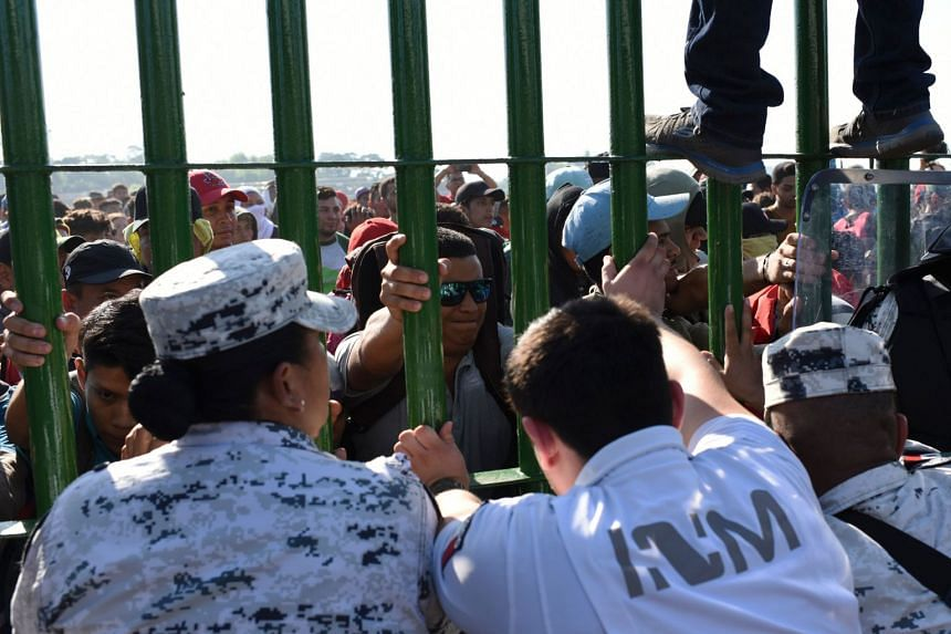 Members of the Mexican National Guard try to prevent Honduran migrants from entering Mexico at a crossing point in Ciudad Hidalgo, Mexico.