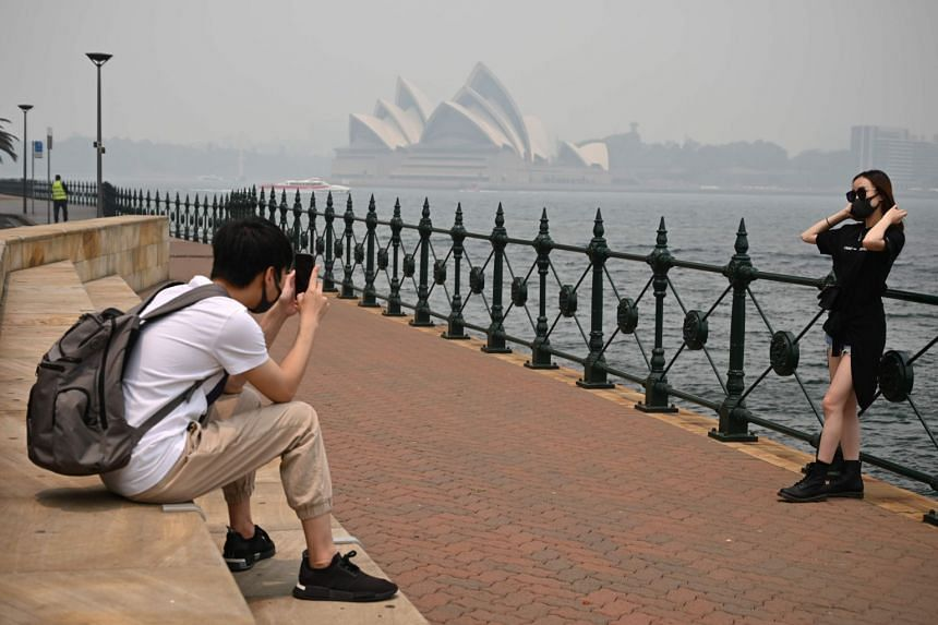 In a photo taken on Dec 10, 2019, tourists wearing masks take photos as the Opera House is enveloped in haze caused by nearby bush fires, in Sydney.