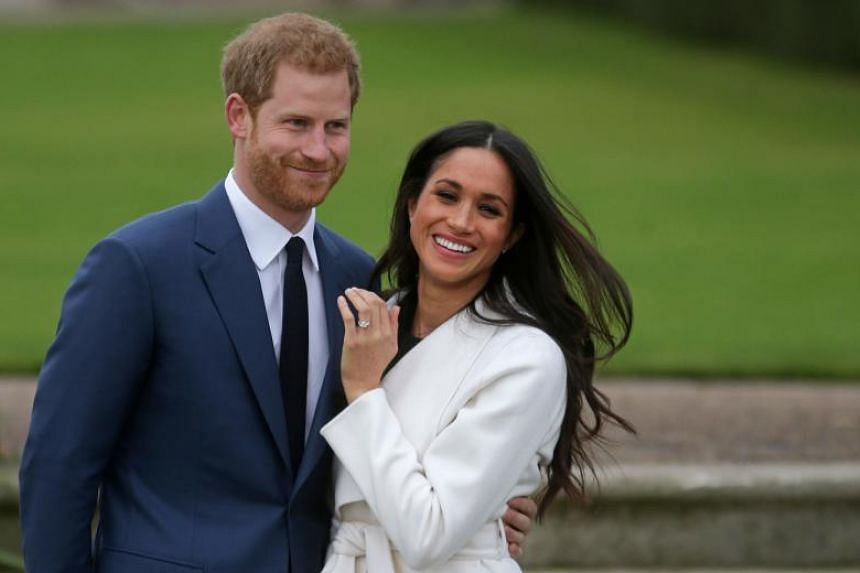In a photo taken on on Nov 27, 2017, Britain's Prince Harry stands with his wife Meghan Markle as she shows off her engagement ring in the Sunken Garden at Kensington Palace.