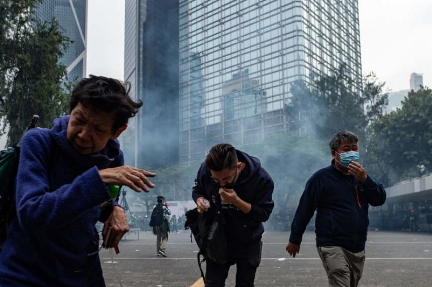 People move away from tear gas fired by police during a rally at Chater Garden in Hong Kong on Jan 19, 2020.