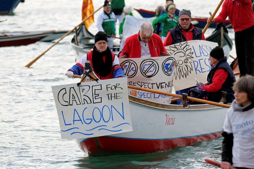 Venetian protesters hold up placards during a protest against the damage caused by big ships in front of Saint Mark's Square in Venice on Jan 19, 2020.