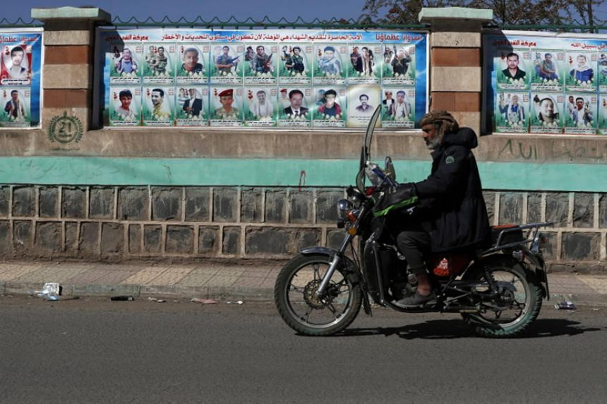 A motorcyclist drives past a wall with banners depicting portraits of late Houthi fighters allegedly killed in Yemen's ongoing conflict, in Sanaa, Yemen, on Jan 18, 2020.