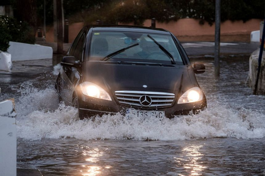 A car drives through a flooded street at Cala de Bou, Ibiza, Balearic Islands, in Spain, on Jan 19, 2020, due to the Gloria squall that affects the region with strong winds, rain and high waves.