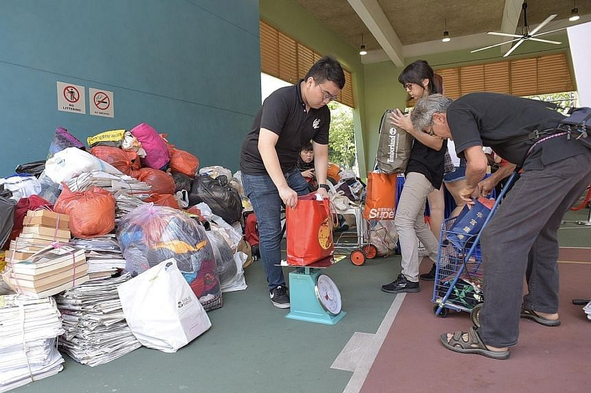 Residents of South West District swopping their recyclables for groceries or vouchers at Chua Chu Kang Community Club yesterday. The annual Clean Up South West! is in its 15th iteration this year.