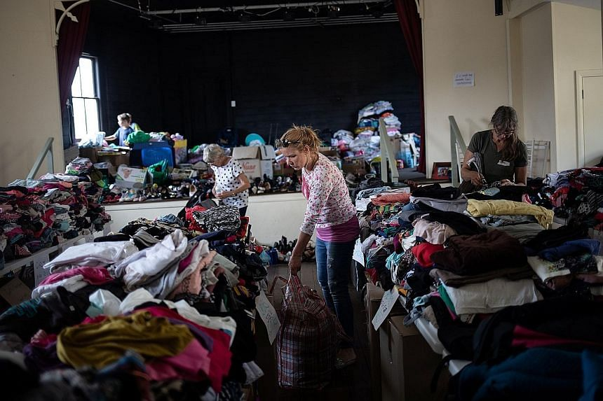 Volunteers arranging donated clothes at a centre in Cobargo town in New South Wales state. As bush fires have ravaged Australia, the outpouring of donations from celebrities, business moguls and people around the world has left the country trying to