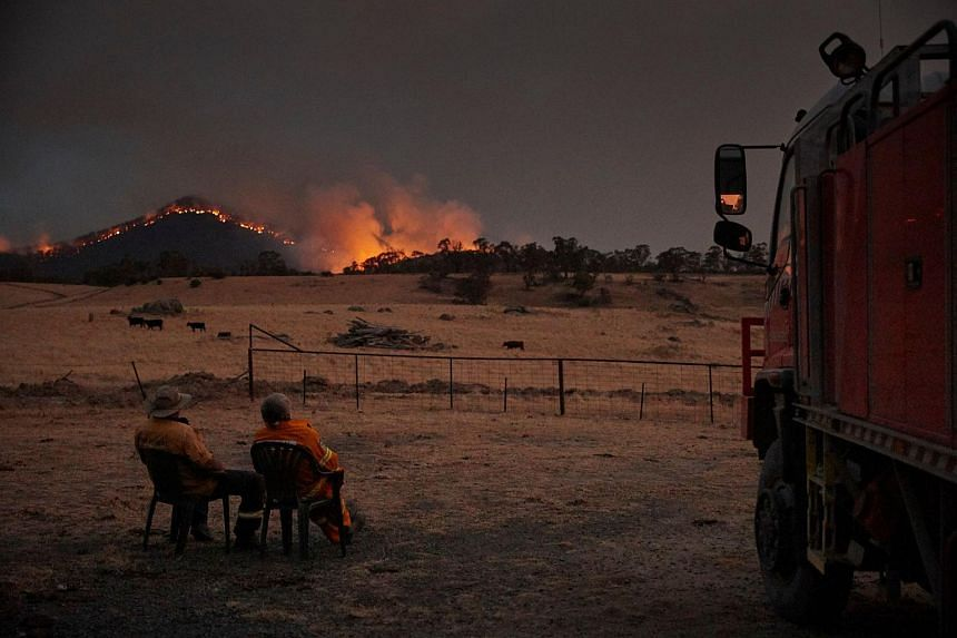 "Rural Fire Service volunteer firefighters watching as the New South Wales ""megafire"" approaches the outskirts of the town of Tumbarumba in New South Wales on 11 Jan, 2020."