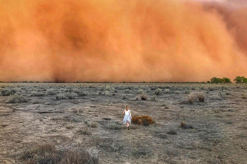 A child running towards a dust storm in New South Wales on Jan 17, 2020.