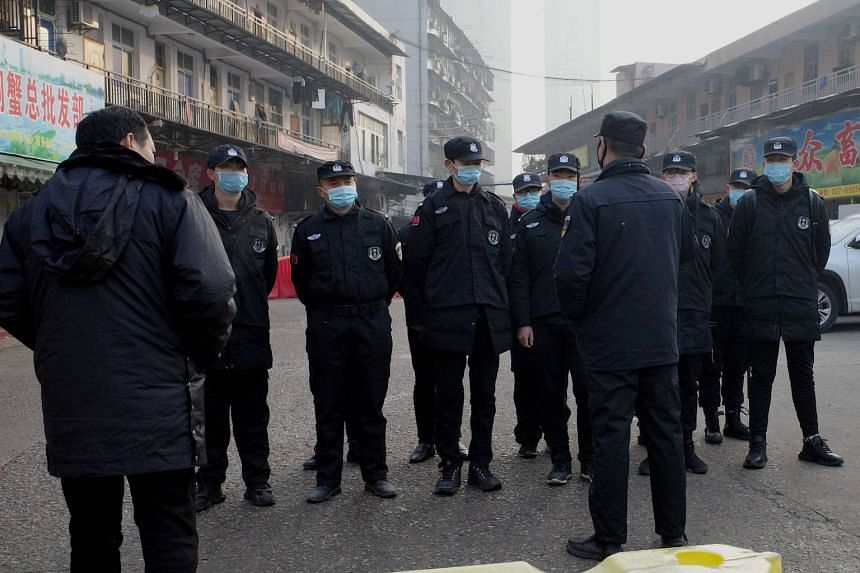 Officials at the Huanan market, where a man who died from a respiratory illness had purchased goods from, in Wuhan, China, on Jan 11, 2020.