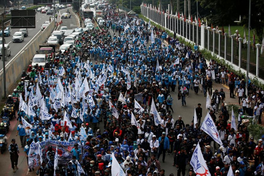 Labourers march outside Indonesia's parliament building in Jakarta on Jan 20, 2020.