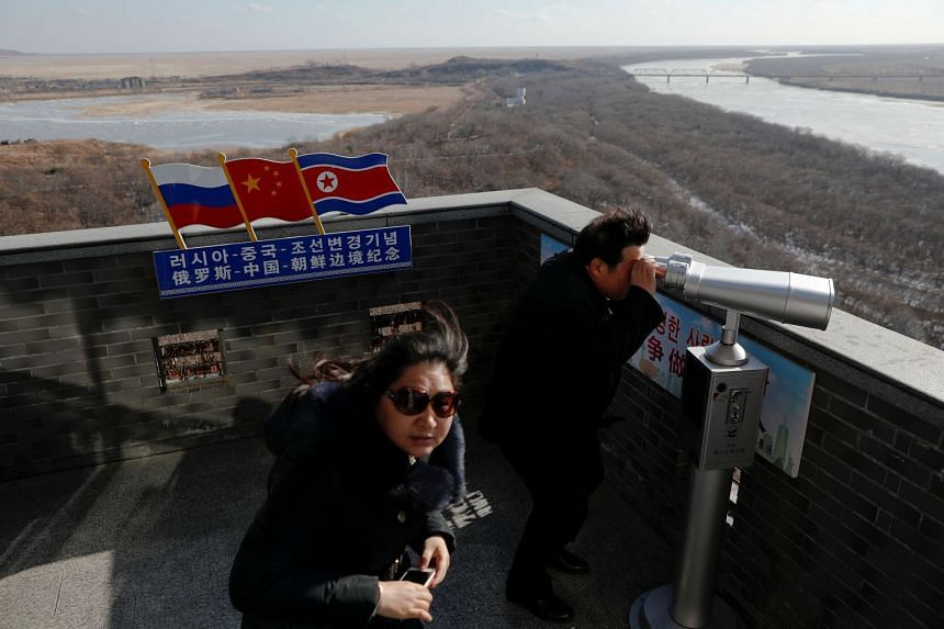 A file photo shows a tourist using binoculars to look across to North Korea from a tower built on the Chinese side of the border between Russia, China and North Korea near the town of Hunchun in China.